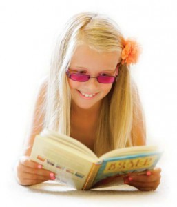 Young girl with tinted glasses reading a book